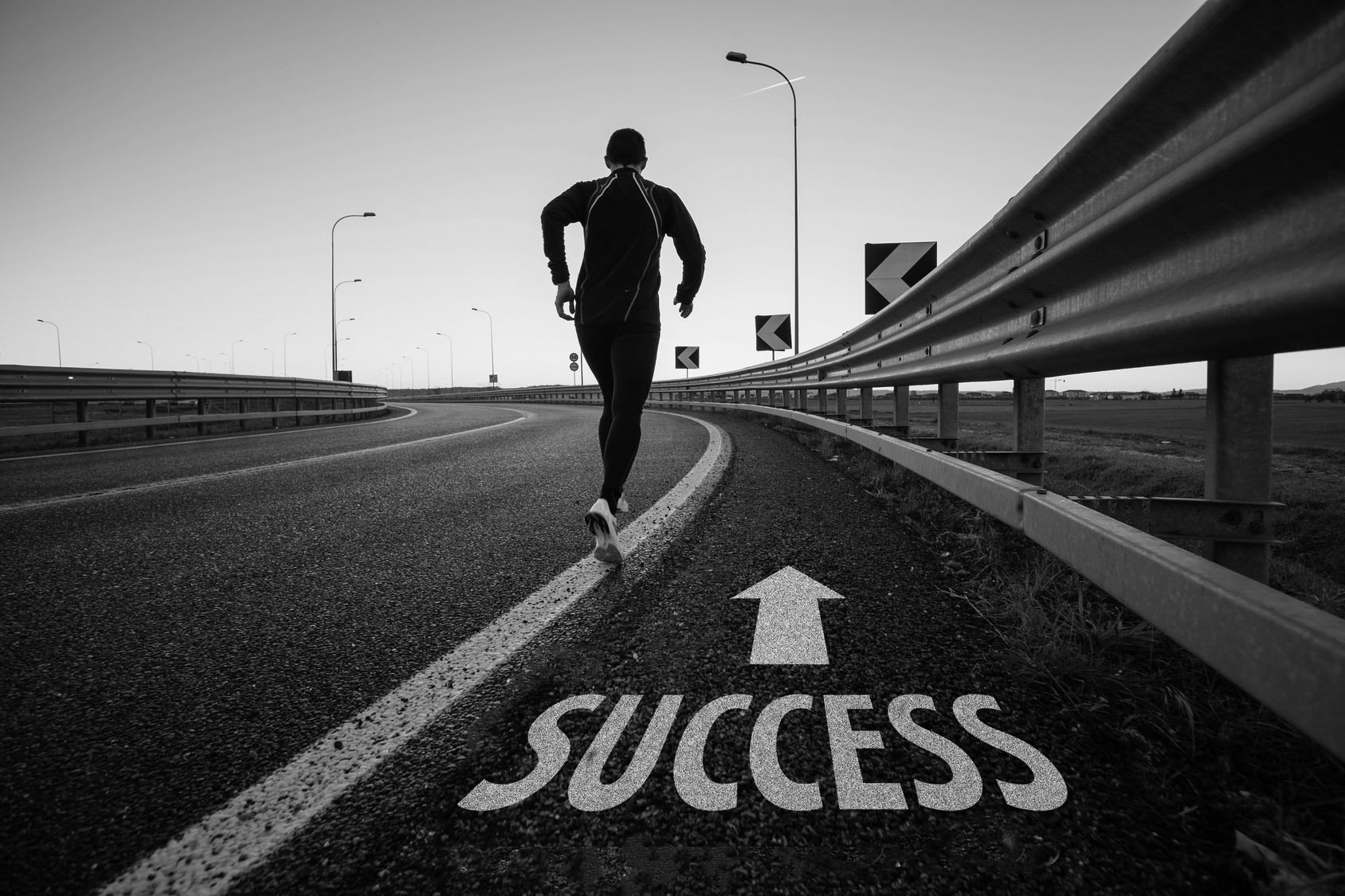 """Man running along a road with the word """"Success"""" and an up arrow painted on it"""